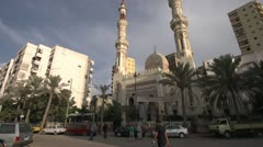 Street traffic in Alexandria, traffic past mosque, wide shot Stock Footage
