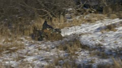 Man on 4 Wheeler ATV Riding on Snowy Trail into Brush on Sunny Day Stock Footage
