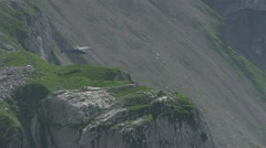 Helicopter hovering near side of mountain Stock Footage