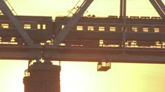 Train rides on an iron bridge at sunset Stock Footage