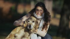 Attractive young woman spending time outdoors with her dog Stock Footage
