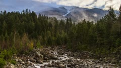 Misty Clouds on a Snowy Mountain Top and River Running Stock Footage