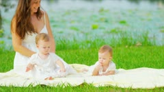 Caucasian twins and mother playing together in garden Stock Footage