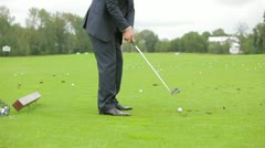 Man in a business suit playing golf - stock footage