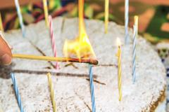 light the birthday candles on the cake - stock photo