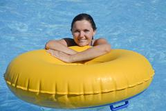 girl in swimming pool with inflatable yellow ring - stock photo