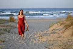 young woman walking back from the sea - stock photo