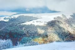 first winter snow in mountain and inclement windy weather beginning - stock photo