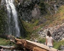 Girl by waterfall - medium shot Stock Footage