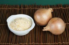 Mature onion and bowl with dried onion powder Stock Photos