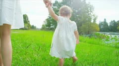 Little girl walking with mother in park holding hands - stock footage