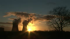 Power station and smoke in evening light with silhouetted tree Stock Footage