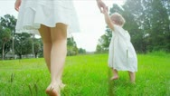 First steps of Caucasian girl walking with mother in park Stock Footage