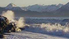 Waves Crashing Against Breakwater with Frothy Spray Mountains Beyond Stock Footage
