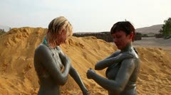 Young woman and woman have mud therapy outdoors summer Stock Footage