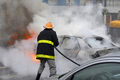 firefighter extinguishing a car fire. last stage of a fire - stock photo