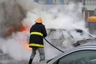 Stock Photo of firefighter extinguishing a car fire. last stage of a fire