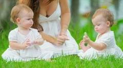 Caucasian mother and babies spending leisure time in garden - stock footage