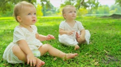 Caucasian girl twins toddling together in garden Stock Footage