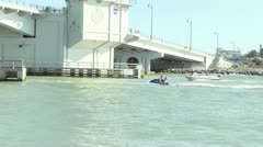 Jet Skier and motorboat pass under a drawbridge Stock Footage