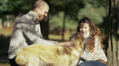 An attractive couple with their pet dog outdoors Stock Footage