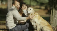 Attractive couple are stroking and petting their pet golden retriever - stock footage