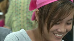 Asian Garment Industry Factory: CU smiling garment worker with pink scarf Stock Footage