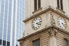 contrast between old church clock tower in front of modern office building - stock photo
