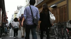 People walking along Japanese narrow alley Stock Footage
