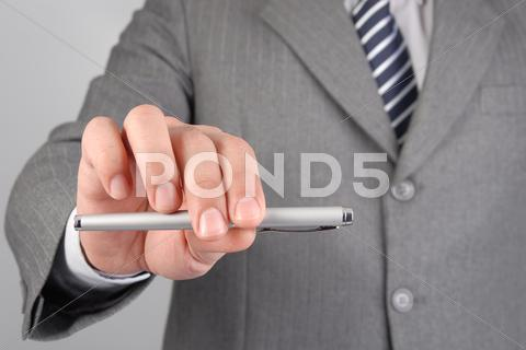 Stock photo of businessman giving you the pen