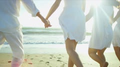 Parents Teenage Daughters Linked Hands Running to Ocean Shallows - stock footage
