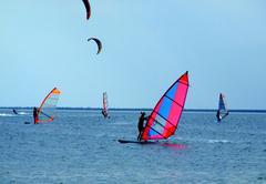 windsurfers and kitesurfers on waves of a gulf - stock photo