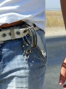 The handcuffs hanging on a belt of jeans Stock Photos