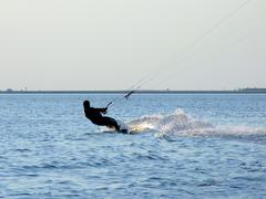 Silhouette of a kite-surf on waves of a gulf 2 - stock photo