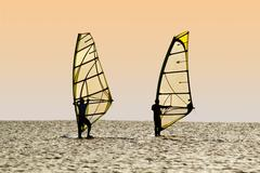 Silhouettes of two windsurfers on waves of a gulf - stock photo