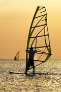 Silhouettes of a windsurfers on waves of a bay - stock photo