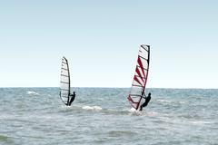 Two windsurfers on waves of a sea - stock photo