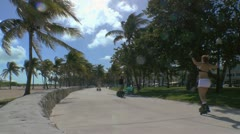 Skateboarding on Lummus park beach walk in Miami Beach Stock Footage