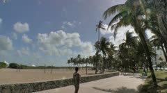 Skateboarding, bicycling along Lummus park beach walk Stock Footage