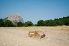 Yellow arrow on a stone, specifying a direction in mountains Stock Photos
