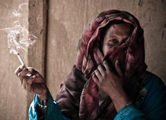 beduin woman who smoke a cigarette - stock photo