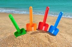 multi-colored children's toys on the beach - stock photo