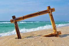 seascape with bamboo frame on the beach sand - stock photo