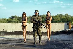 Soldier and two women Stock Photos