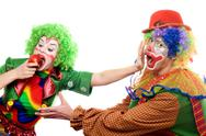 Stock Photo of Clowns are fighting for an apple