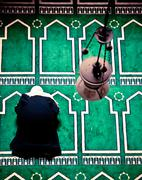 Woman is praying in door in the mosque on mat Stock Photos
