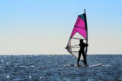 Silhouette of a girl windsurfer - stock photo