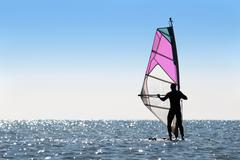 Silhouette of a woman windsurfer - stock photo