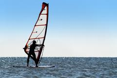 Silhouette of a windsurfer on the blue sea - stock photo
