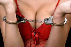 young woman in red lingerie handcuffed - stock photo